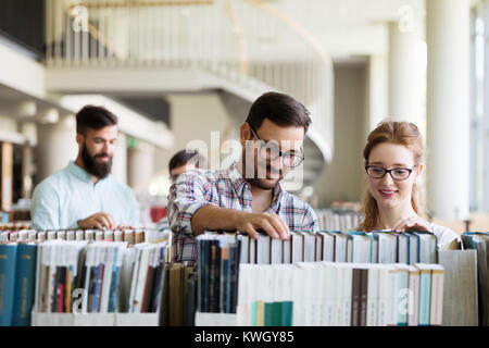 Happy young university students studying with books in library - Stock Photo