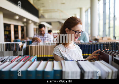Portrait of a pretty smiling girl reading book in library - Stock Photo