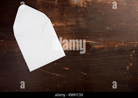 a blank empty card envelop on a wooden table background with copyspace to the left - Stock Photo
