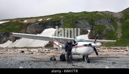 K-Bay Air airplane (Cessna 206) and pilot standing on a beach filled with driftwood in the Katmai National Park - Stock Photo