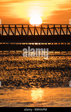 Sunset over a beach with the tide out in Winter, with the sun reflecting in wet sand, in the UK. - Stock Photo