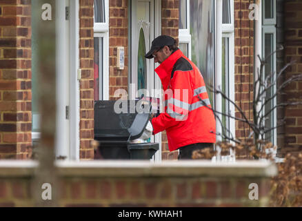 Royal Mail postman delivering post through a letter box to a house in England, UK. - Stock Photo
