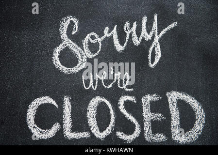 Sorry we're closed is shown written in white chalk on a blackboard - Stock Photo