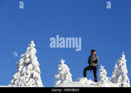 Woman hiker in active outfit standing on a hill covered with snow between spruces in daylight with moon on the blue - Stock Photo