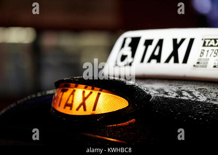 yellow taxi rooftop for hire light at night in the rain belfast northern ireland uk - Stock Photo