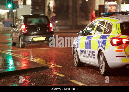 police vehicle following car at night in city centre belfast northern ireland uk - Stock Photo