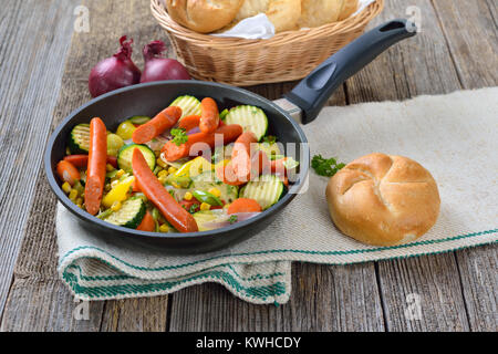 Short fried Vegetables with spicy Debreziner sausages served in a frying pan - Stock Photo