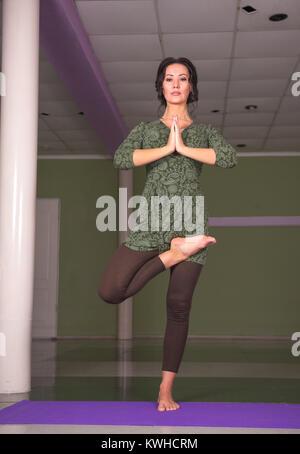 Woman showing yoga asana in a studio - Stock Photo