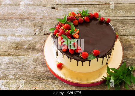 Beautiful festive cake covered with melted chocolate with strawberries and mint leaves - Stock Photo