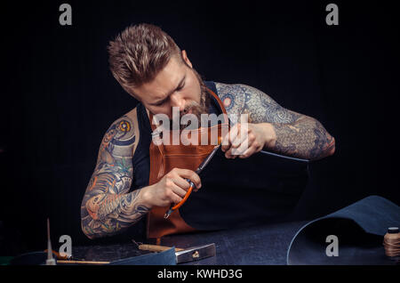 Leather master working on a new leather product  - Stock Photo