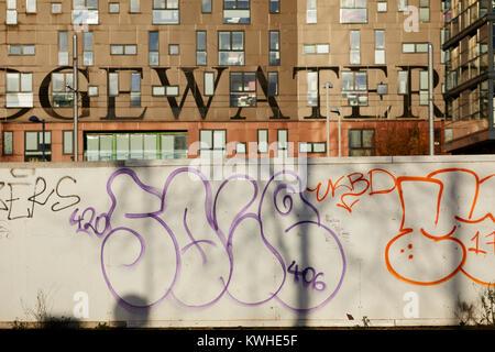Graffiti 'throwups' spray painted street art on development Hoarding boards in New Islington, East Manchester - Stock Photo
