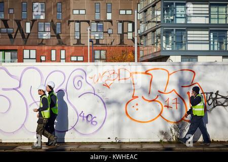 Graffiti 'throwups' spray painted street art on development holding boards in New Islington, East Manchester workmen - Stock Photo