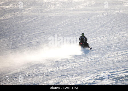 Snowmobile racing across a snow covered frozen Lake Pleasant in the Adirondack Mountains, NY USA stirring up a cloud - Stock Photo