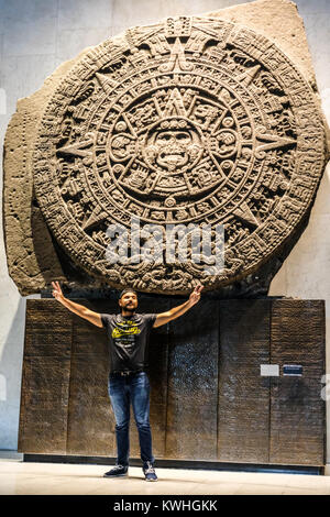 Tourist posing in front of the Sun Stone at the National Museum of Anthropology of Mexico - Stock Photo