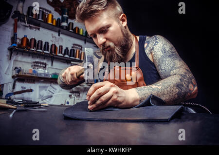 Close up of a shoemaker man working with leather - Stock Photo