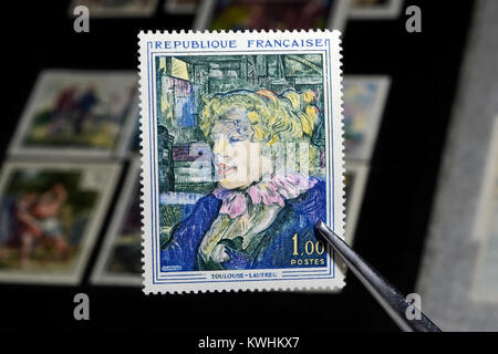 Tweezers hold a colorful postage stamp printed by France, Shows Toulouse Lautrec - Stock Photo