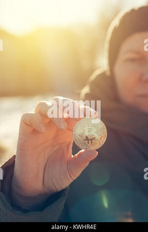 Bitcoin cryptocurrency in hands. Woman holding BTC golden coin as symbol of electronic virtual money for web banking - Stock Photo