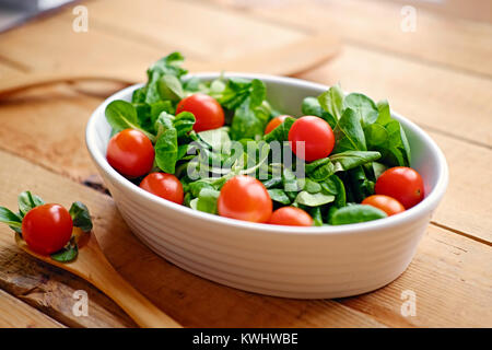 Cherry tomatoes and basil salad in a white cup on a wooden table - Stock Photo
