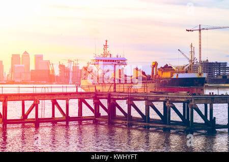 Sunset casting a pink light on a disused jetty adjacent to the Thames Barrier in London with an approaching ship - Stock Photo
