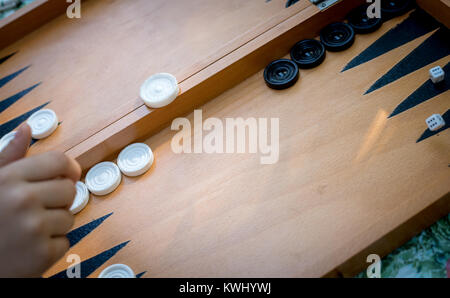Hand throwing  dice on a  wooden backgammon board  playing  backgammon  game. - Stock Photo