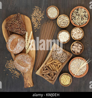 High fibre health food with whole grain bread, pasta, cereals and grains on an olive wood board and in wooden and - Stock Photo
