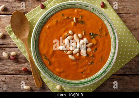 Vegetarian West African Peanut Soup close-up in a plate. on the table. horizontal top view from above - Stock Photo