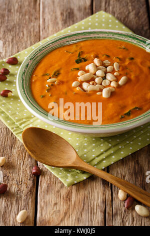 West African peanut soup with kale closeup on a plate on a table. vertical - Stock Photo