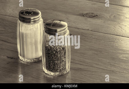 Close up of glass salt and pepper shakers or salt and pepper pots on a wooden table . - Stock Photo