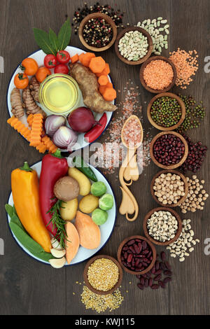 Health food concept with fresh vegetables, pulses, herbs, spice, himalayan salt and olive oil with foods high in - Stock Photo