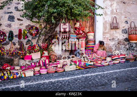 A vendor sells souvenirs for tourists in front of a colonial home in Taxco de Alarcon, Guerrero State, Mexico - Stock Photo