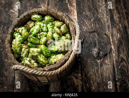 Green hops for beer in a wooden bucket. On a wooden background. - Stock Photo