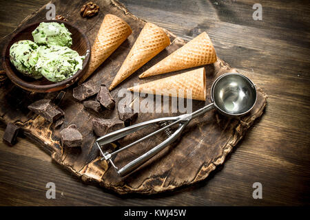 Fresh pistachio ice cream in a bowl with waffle cups. On a wooden table. - Stock Photo