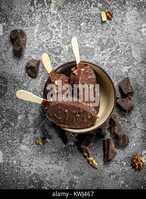 Fresh ice cream on a stick in chocolate with nuts. On a rustic background. - Stock Photo