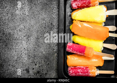 Multicolored fruit ice made from fruits. On a rustic background. - Stock Photo