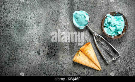 Fruit ice cream in a bowl with a spoon and waffle cups. On a rustic background. - Stock Photo