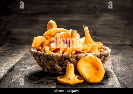 Mushrooms chanterelle in the basket. On a wooden background. - Stock Photo