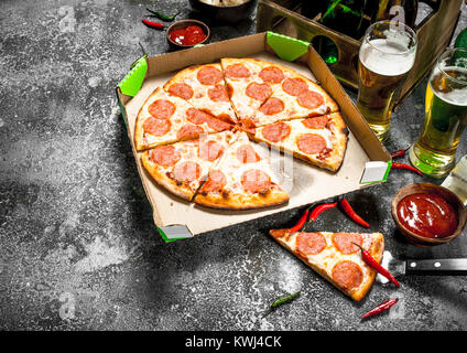 Pizza background. Pepperoni with beer. On a rustic background. - Stock Photo