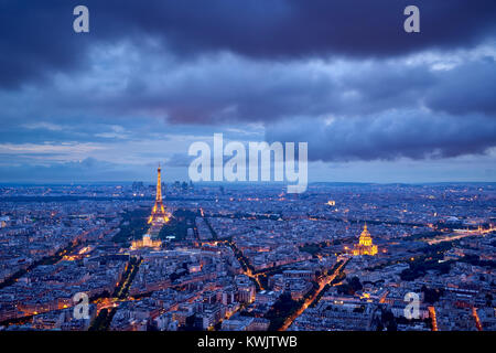Aerial view of Paris rooftops and monuments (illuminated Eiffel Tower and Les Invalides) at twilight. 16th and 7th - Stock Photo