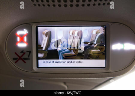 Recorded screening of aeroplane aircraft airplane air plane flight monitor screen showing pre flight passenger safety - Stock Photo
