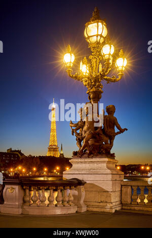 Pont Alexandre III Bridge candelabra style lamp post with the illuminated Eiffel Tower. 8th Arrondissement, Right - Stock Photo