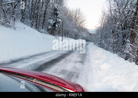 Icy slippery snow covered French alpine country road, with ice, after a blizzard, seen through the windscreen from - Stock Photo