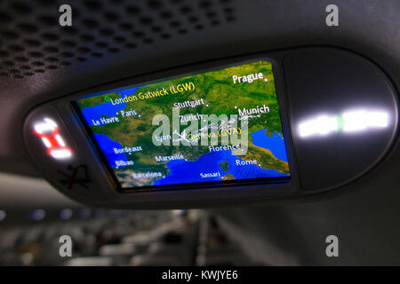 Aeroplane / air plane cabin flight position map display on TV screen showing aircraft postion above / over France - Stock Photo