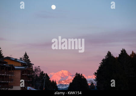 View of the waxing gibbous moon (nearly full moon) rising at sunset over the Alps as seen from Plateau De Sur Lyand, - Stock Photo