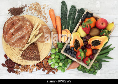 High fibre healthy food concept with wholegrain bread and rolls, nuts, seeds, fruit, vegetables and grains. - Stock Photo
