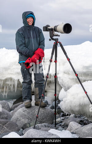 Photographer with huge telephoto lens capturing wildlife; Half Moon Island; Antarctica - Stock Photo