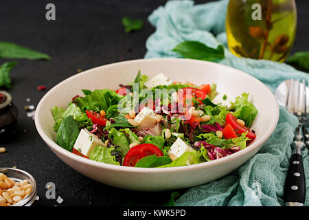 Dietary salad with tomatoes, feta, lettuce, spinach and pine nuts. - Stock Photo