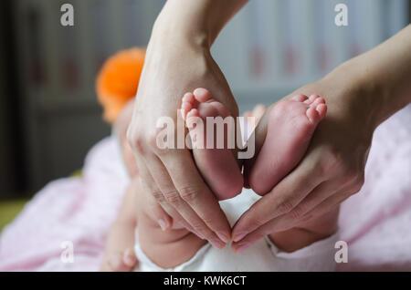 Baby feet in mother hands.baby is sleeping - Stock Photo