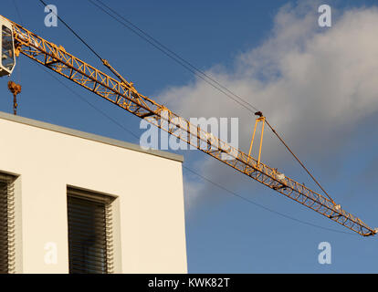 crane boom in front of a bright blue sky above the corner of a new building, abstract - Stock Photo