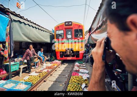 Maeklong, Thailand - November 4, 2017: Railway market on November 20, 2017 near Maeklong station. Train passing - Stock Photo
