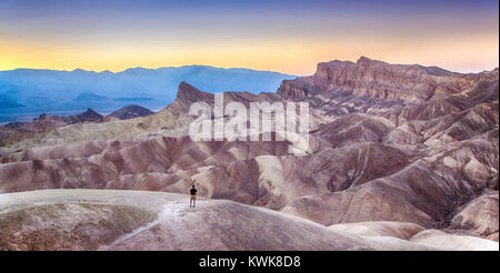 Panoramic view of a hiker standing at famous Zabriskie Point viewpoint in golden evening light at sunset, Death - Stock Photo